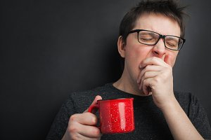 Sleepy yawning man in eyeglasses with red cup of tea or coffee has uncombed hair in underwear on black background, morning refreshment and drink. Copy space for your text
