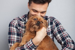 Closeup portrait handsome young hipster man, kissing his good friend red dog isolated light background. Positive human emotions, facial expression, feelings