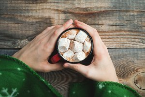 Male hands holding red mug with cocoa and marshmallows on wooden background. top view with copy space