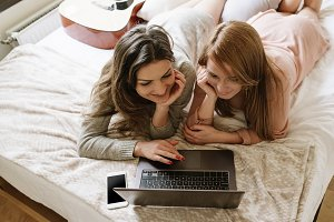 Gorgeous friends using the laptop.