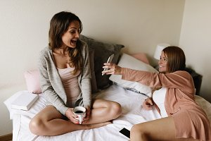 Friends using mobile in the bedroom.