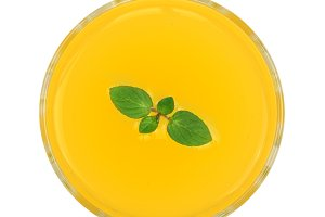 orange or pineapple juice in a glass with mint leaves isolated on white background. Top view