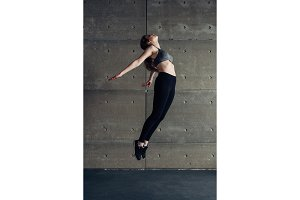 Sports young woman doing back bend jump