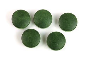 Spirulina tablets algae nutritional supplement isolated on white background close up top view. Flat lay