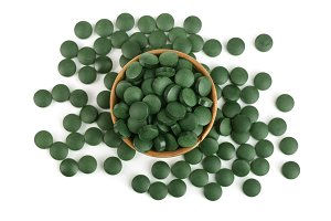 heap of Spirulina tablets algae nutritional supplement in wooden bowl isolated on white background close up top view