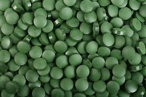 heap of Spirulina tablets algae nutritional supplement as a background close up top view. Flat lay