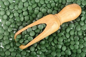 heap of Spirulina tablets algae nutritional supplement in wooden scoop as a background close up top view. Flat lay