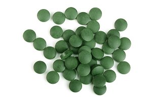 heap of Spirulina tablets algae nutritional supplement isolated on white background close up top view. Flat lay