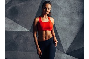 Portrait of fit woman standing, posing, showing her muscular body. Fitness and sport