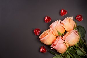 five beige rose with candles in the shape of heart on a dark wooden background with copy space for your text