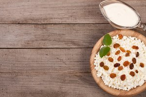 Cottage cheese in bowl with sour cream and raisins on old wooden background with copy space for your text. Top view