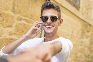 young man holding his hand talking on the phone