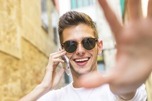 portrait of young smiling with the mobile phone in the city