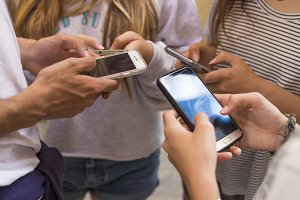 group of young people with mobile phones on the street