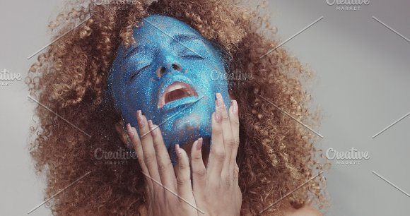 Black Woman With Blond Hair And Blue Glitter Face Makeup
