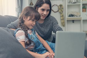 young mom and daughter use notebook
