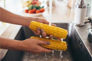 Woman rinsing fresh corns by hands in the kitchen-sink. Going to prepare salad.