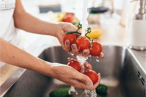 Woman washing tomatoes in kitchen sink close up.