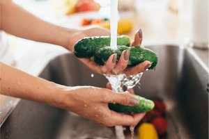 Woman washing cucumbers in kitchen sink close up.