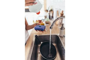 Woman putting cleanser to a sponge to wash pan in the kitchen-sink. Hand washing dishes. Close-up.