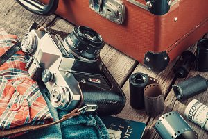 Old suitcase, clothing and camera
