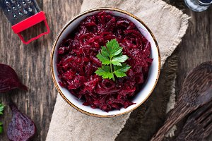 Bowl of beetroot salad on wooden background