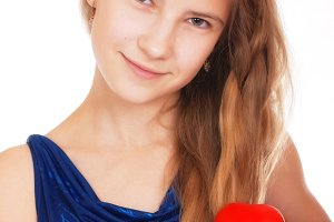 Valentine's day. Smiling beautiful teen girl with a symbolic gift in the form of a red heart