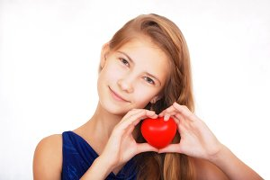 Smiling beautiful teen girl with a symbolic gift in the form of a red heart