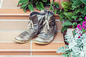 Old worn out boots at doorstep