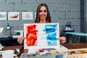 Pretty smiling woman holding a finished watercolor illustration of the flag of France standing in art school classroom