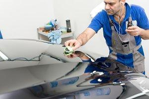Man on a car wash polishing car with