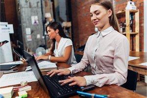 Friendly female office workers wearing formal workwear typing on laptop keyboard working in creative agency