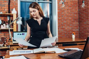 Serious woman reading papers studying resumes standing at work desk in stylish office