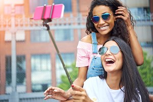 Carefree young girlfriends laughing and taking selfies outside