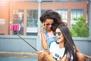 Smiling young girlfriends laughing and taking selfies together outside