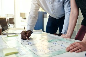 Designers studying building plans at an office desk