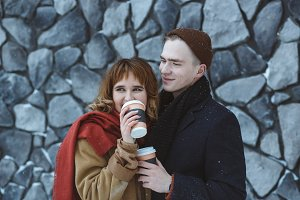 Happy emotions of couple in love spending time together and drinking coffee outside during winter. Urban stone wall background