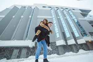 Active young couple running, jumping and enjoying together in winter city background