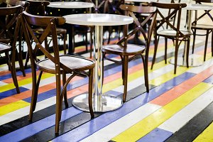 Photo of cafe with chairs, tables on multi-colored floor