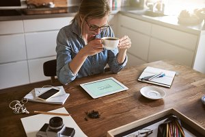 Young woman drinking coffee and working online at home