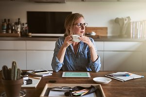 Young woman drinking coffee and thinking while working from home