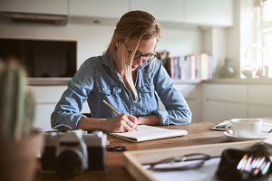 Young woman sketching in a notepad while working at home