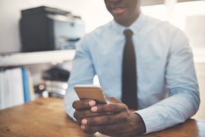 African businessman sending texts on a cellphone in an office