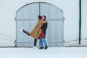 Stylish couple in classic winter clothes embracing near white historical building