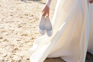 Wedding warm white shoes in bride's hands on the beach.