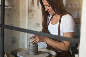 Female artisan creatively sculpting clay in her pottery workshop