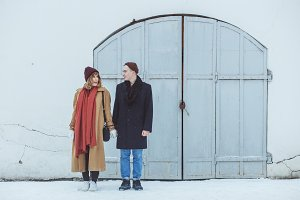Stylish couple in classic suite standing near white historical building. Fashionable winter clothing