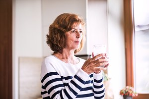 Senior woman holding a glass of water in the kitchen.