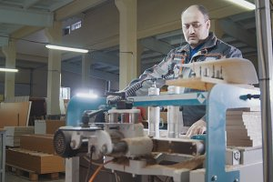 Worker carpenter cut a wooden workpiece on a furniture factory