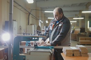 Worker carpenter cut a wooden fragment on a furniture factory